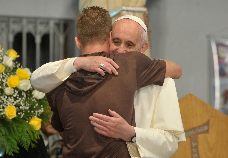 Nella foto: Papa Francesco che abbraccia un ragazzo