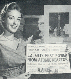 Smiling woman displaying newspaper headline