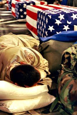 Army Sgt. Osvaldo Ortiz sleeps next to the fla...