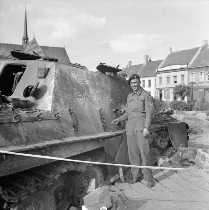 A British soldier poses next to a knocked out Jagdpanther