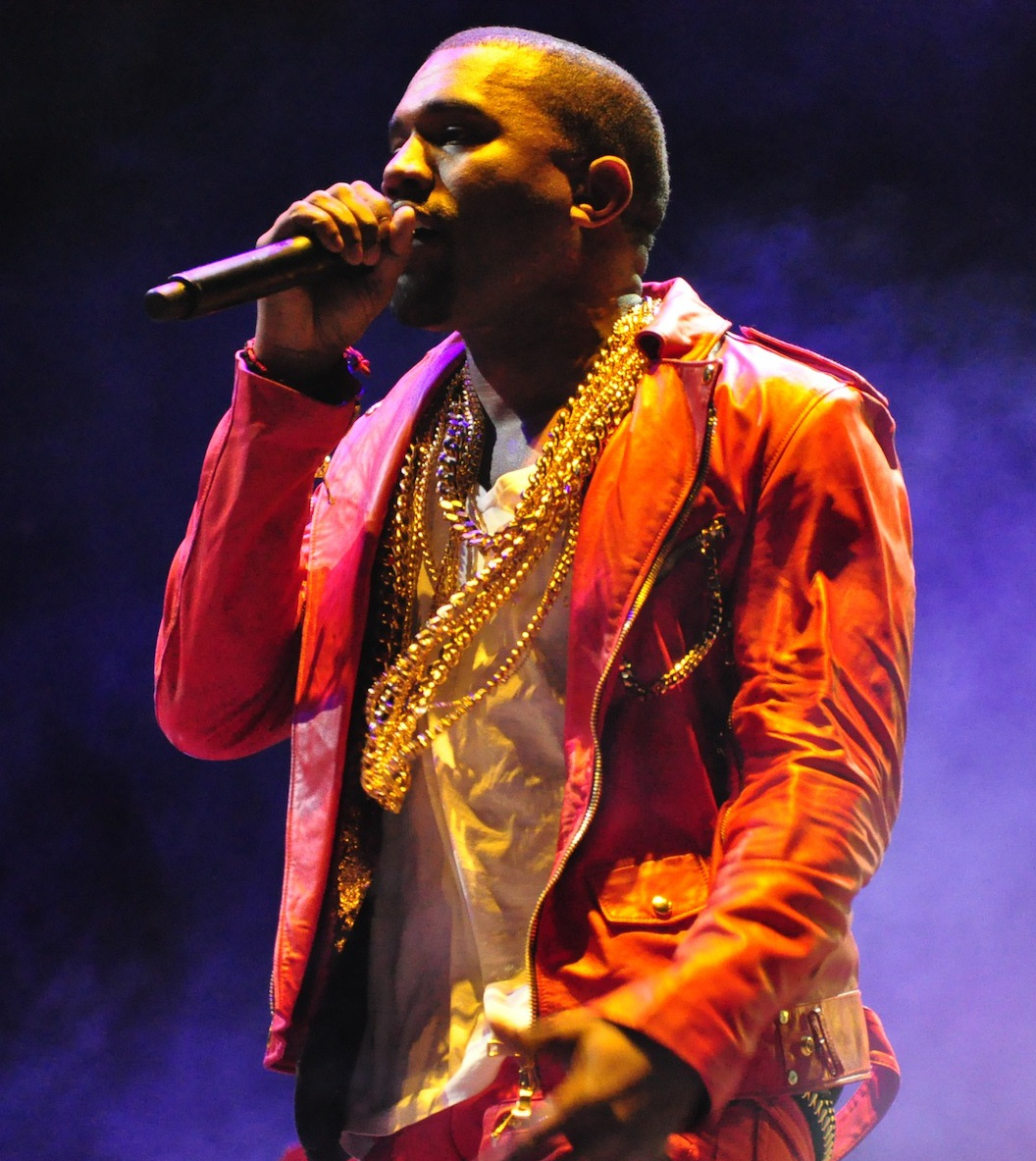 Kanye West; man in orange jacket with microphone