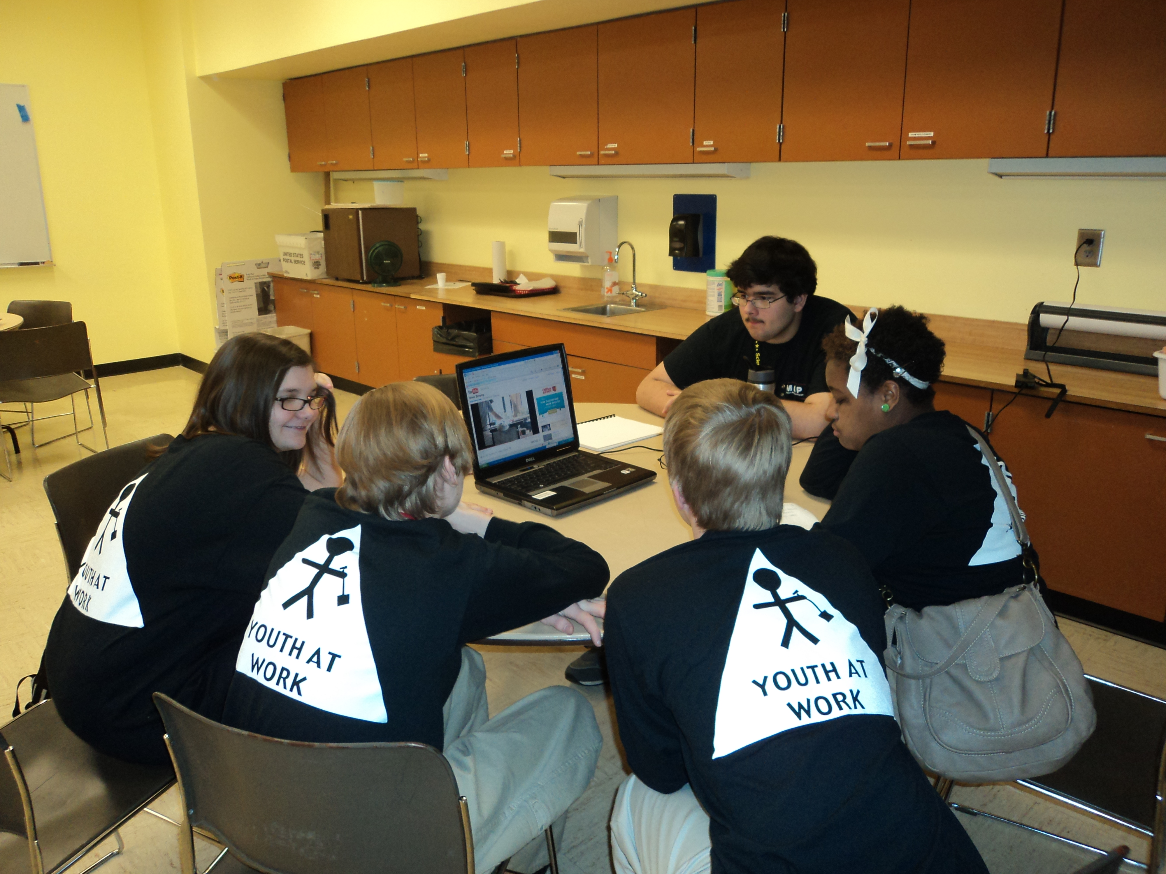 "A group of students at a laptop at the Children's Museum of Indianapolis wearing ""Youth at work"" t-shirts"