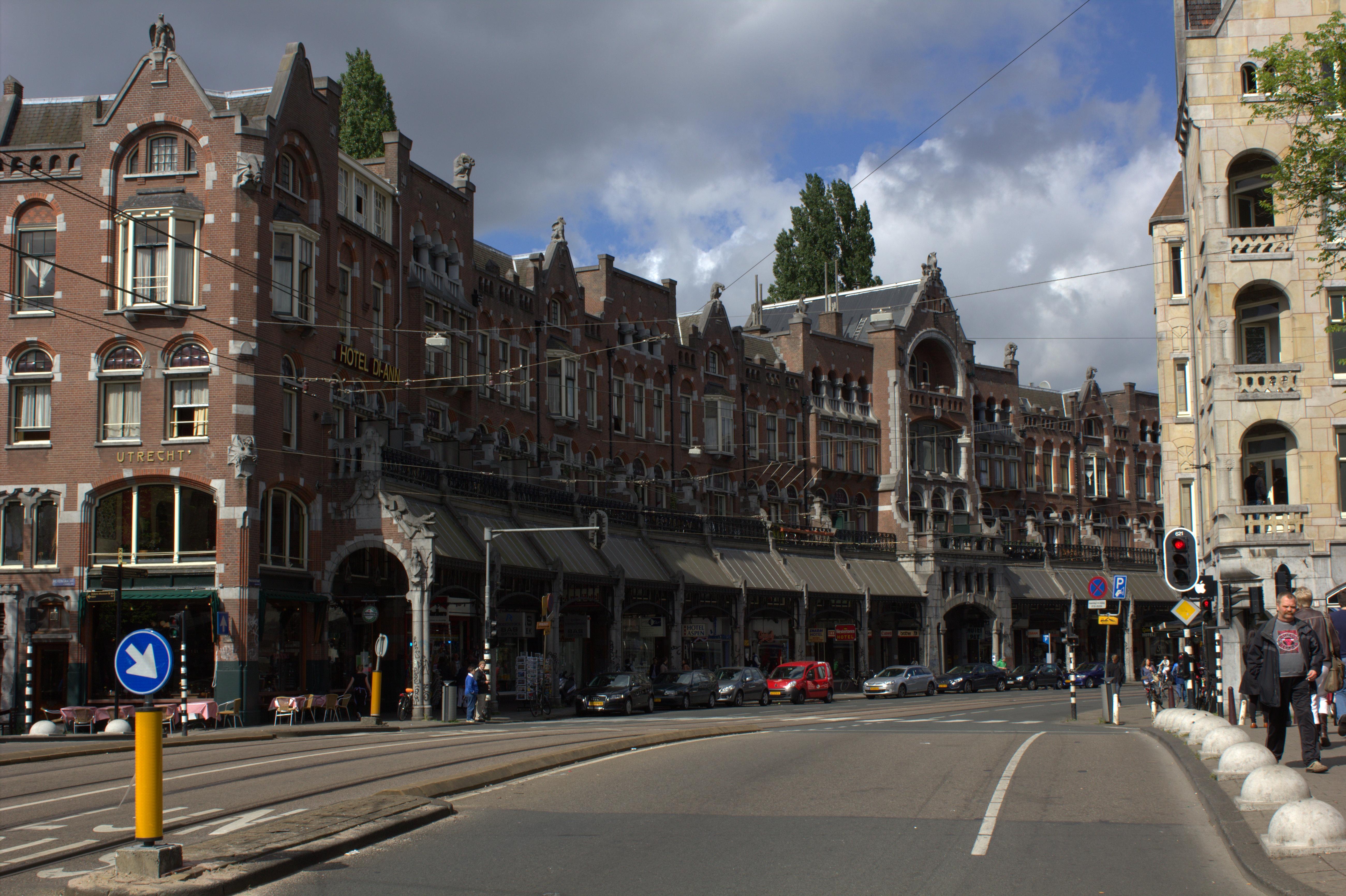 In boogvorm gebouwde reeks winkelwoningen van vier bouwlagen met uitgebouwde galerij op de - Afgeronde bank ...