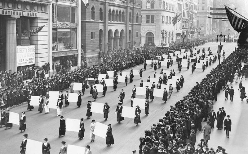 omenssuffragistsparadeineworkityin1917,carryingplacardswiththesignaturesofmorethanamillionwomen.refref