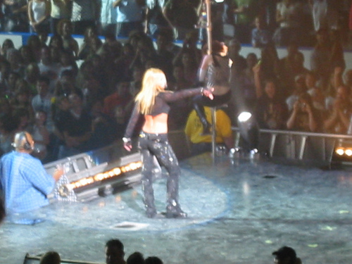 Image of a blond female performer. She is turning her back to the camera, near the end of the stage. She is wearing black pants and a black top with long sleeves, showing her midriff. In front of her, a female dancer is climbing into a pole. A crowd of people clapping, screaming and taking pictures stands can be seen in the audience.