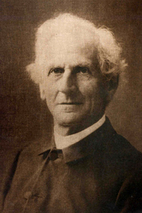 monochrome photograph of an elderly man wearing austere clerical clothing