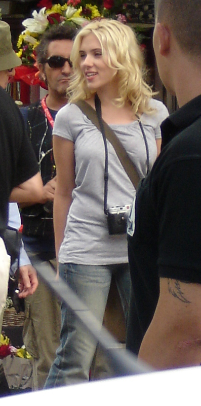 A young woman with tousled medium length blonde hair loosely around her shoulders and face, looking to her right, her right arm slightly behind her, stands in the middle of a group of men. She is dressed in denim jeans, a light gray short sleeved shirt and a camera hangs around her neck.