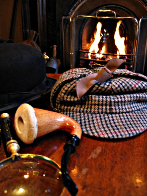 A magnifying glass, a meerschaum pipe, and a deerstalker cap on a table in front of a fire