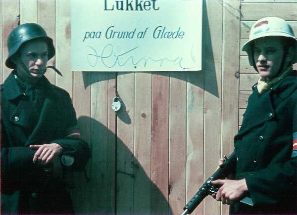 Closed on account of happiness. Two Danish resistance fighters are guarding a shop while the owner is celebrating the liberation of Denmark on 5 May 1945. The man on the left is wearing a captured German Stahlhelm, the one on the right is holding a Sten gun Closed due to happiness.jpg