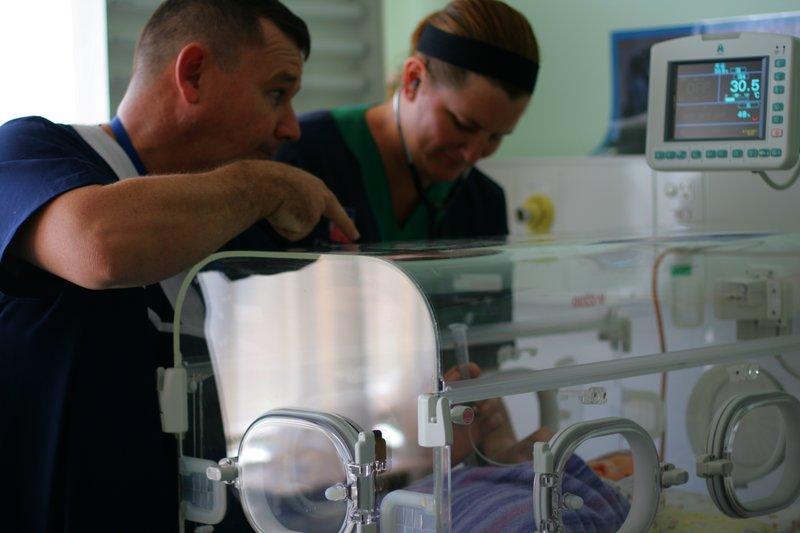Sick baby with nurses.jpg