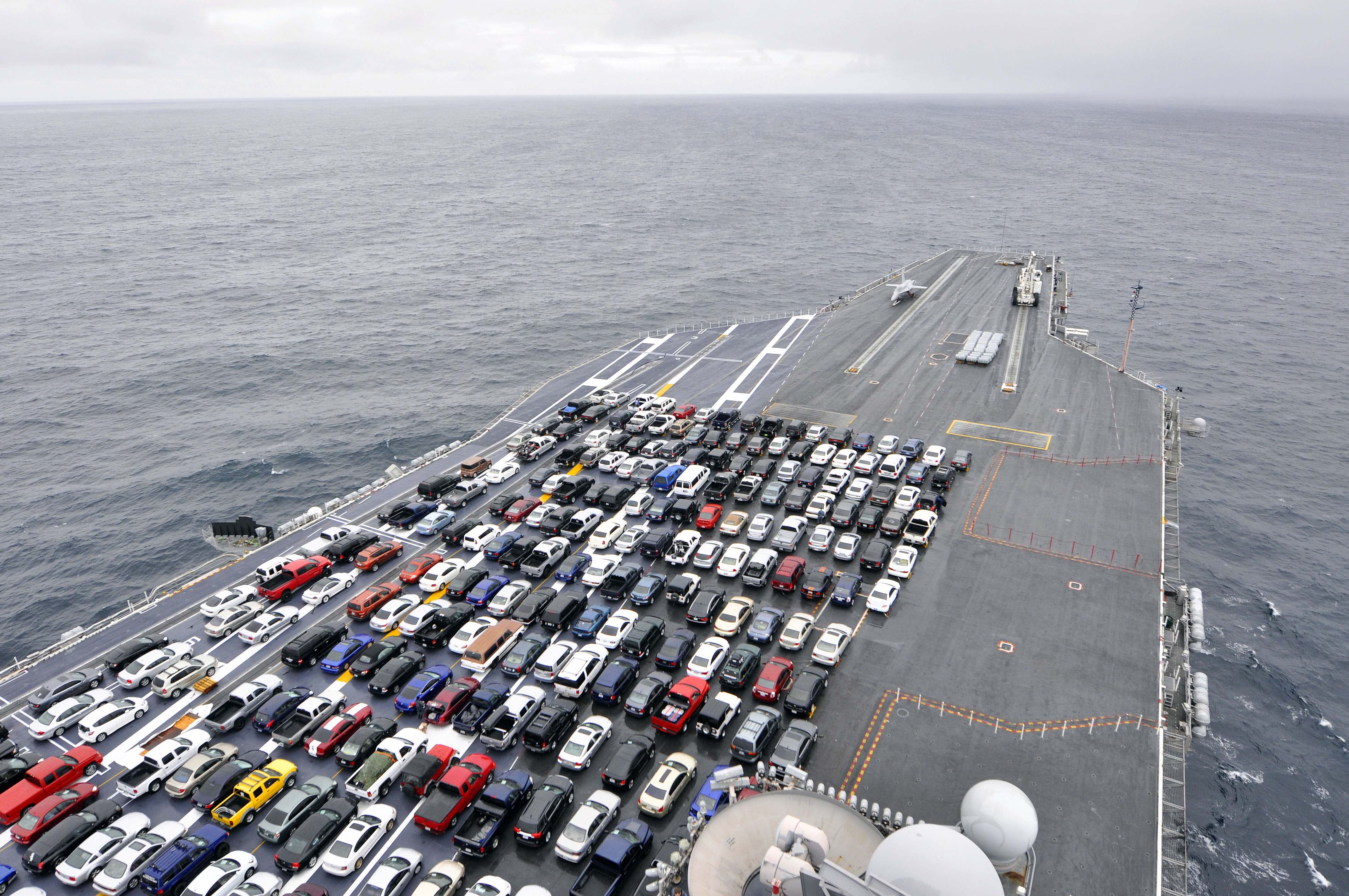 The crew's cars parked on the deck of USS Reagan as it ...