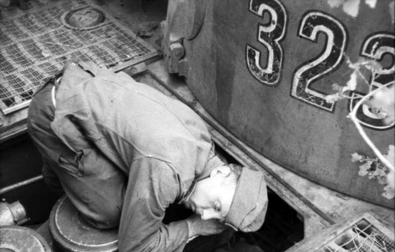 A technician at work on Tiger 323 of schwere Panzer-Abteilung 503