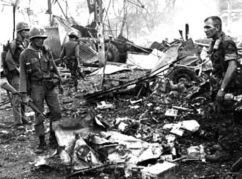ARVN Forces and a US Advisor inspect a downed helicopter, Battle of Dong Xoai, June 1965 DongXoaiHuey-65a.JPG