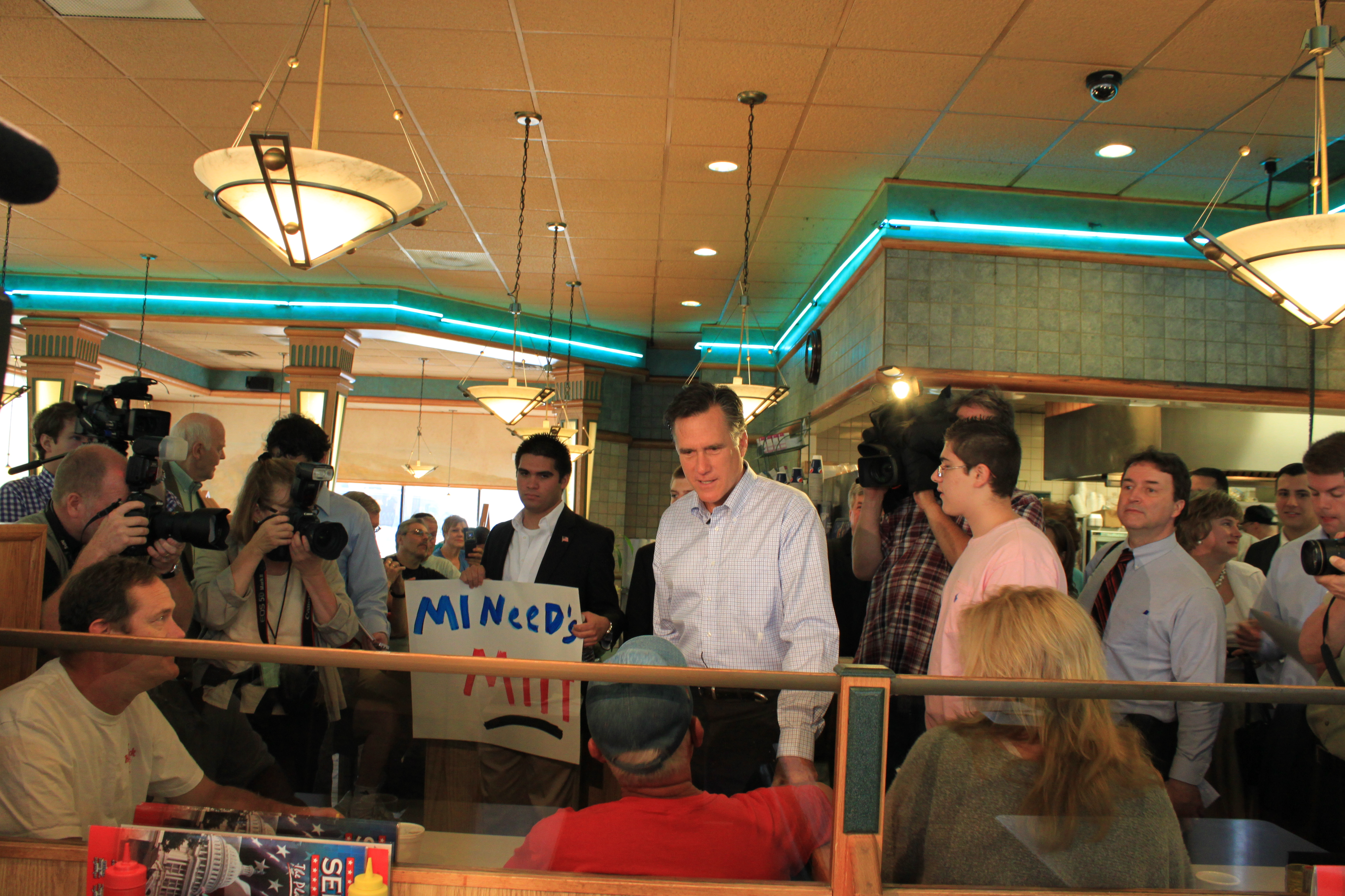 Photograph of Romney working a lunch counter line, with citizens and press photographers crowding around