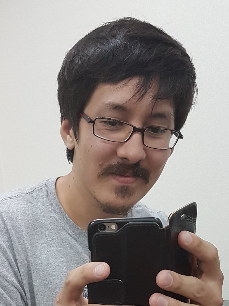 Ronald Watkins pictured from the shoulders up, wearing a gray t-shirt and glasses. He is holding and looking at a cell phone in a black folding case.