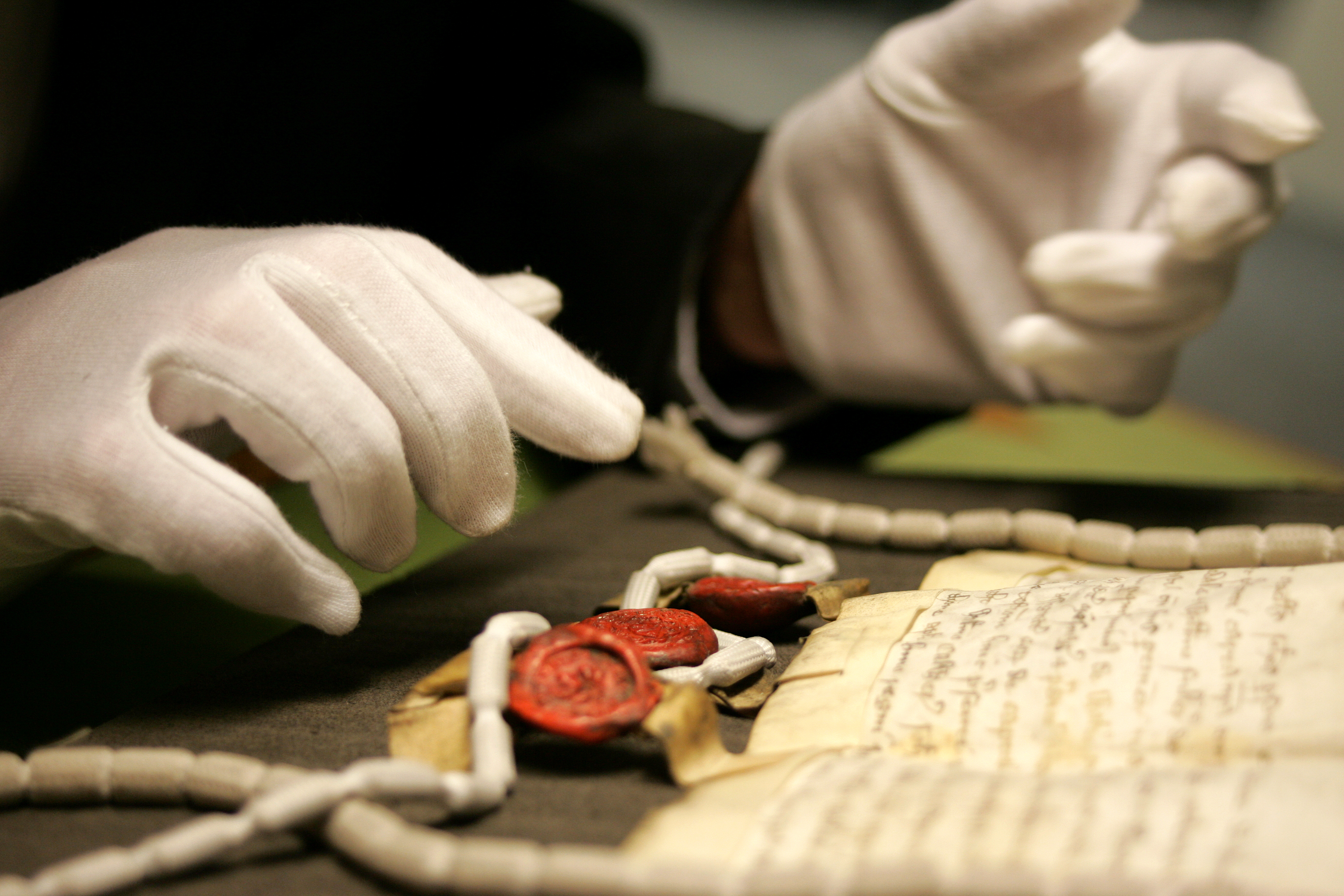 A manuscript and seals being examined at the archives