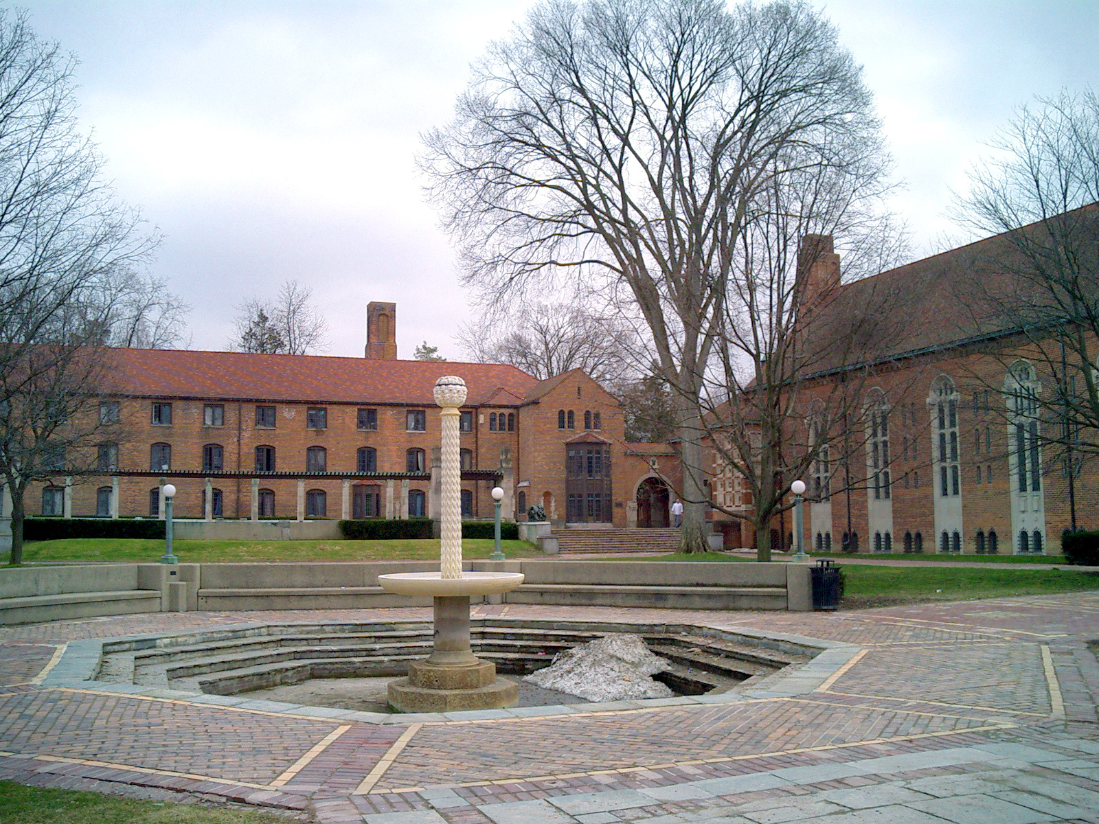Several three-story brick buildings surrounding a large courtyard with fountain