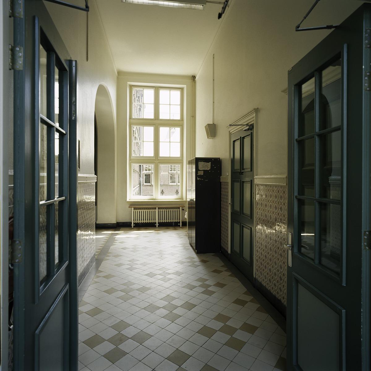File interieur overzicht van een gang met een lambrisering van geglazuurde tegels en tegelvloer - Een gang ...