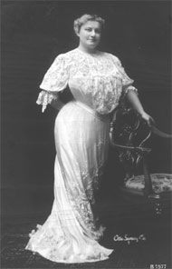 Irwin in an ornate white dress, leaning against a chair