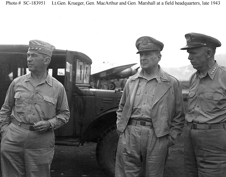 Three men in Army uniforms with open neck shirts. Krueger wears a garrison cap, MacArthur his special cap, and Marshall, a peaked cap. in the background there is a truck and a propeller driven airplane.