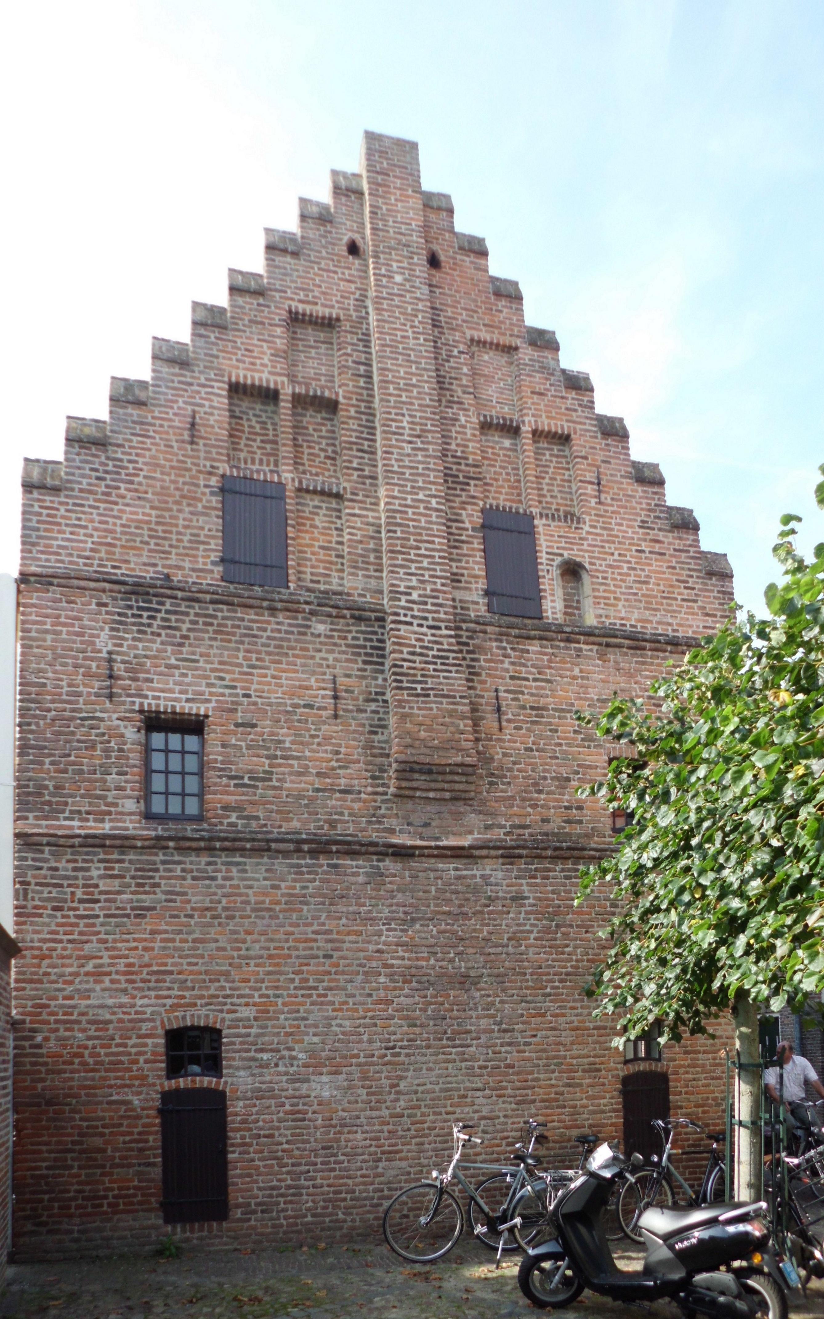 Middeleeuws huis met zadeldak tussen een puntgevel met ezelsrug en uitgekraagde hangtorentjes op - Tussen huis ...