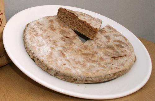 スコットランド、オークニーの伝統的な六条大麦(beremeal)のバノック。切り分けられた一片はスコーンと呼ばれる。