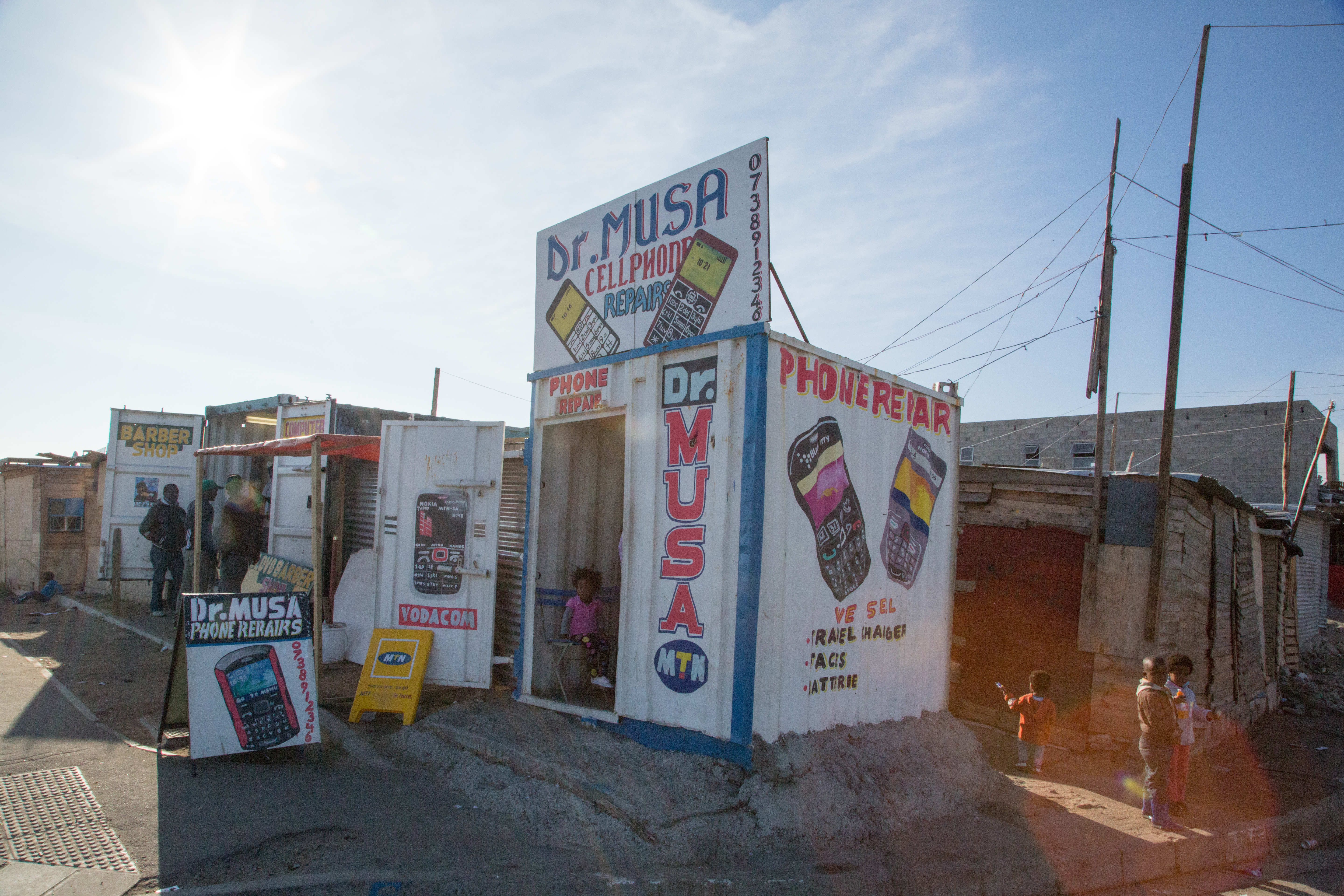 A cellphone repair shop built from a shipping container in Joe Slovo Park. The store is across the street from the school.