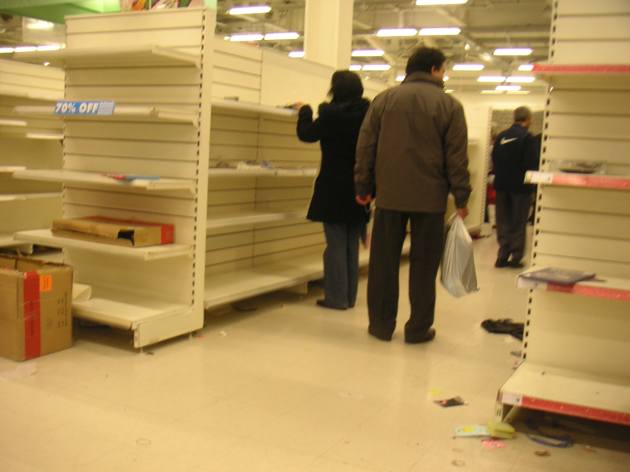The last day at Woolworth's and there are a few shoppers browsing the very few items left on the shelves.