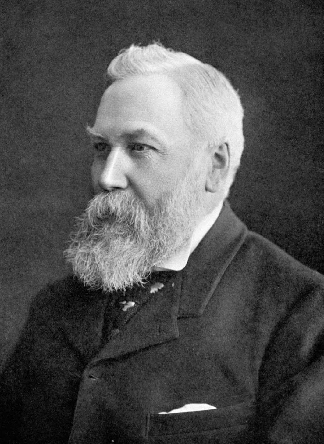 A head and shoulders view of an elderly man with white hair and a large, bushy beard. He is wearing a dark jacket and tie and a white shirt