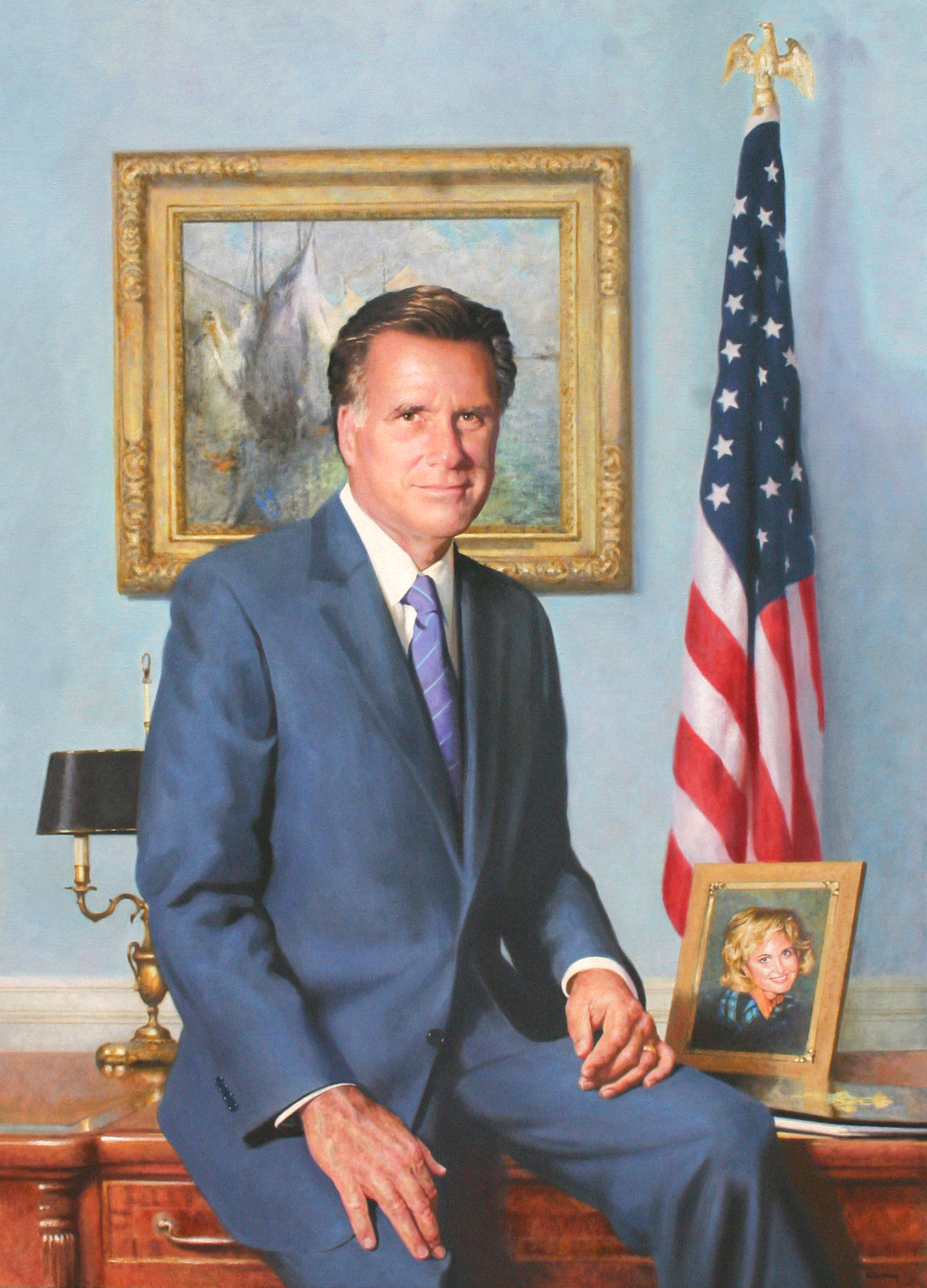 Mitt Romney resting on a wooden desk, flanked by an American flag, a picture of his wife, a lamp, and a painting of mountains