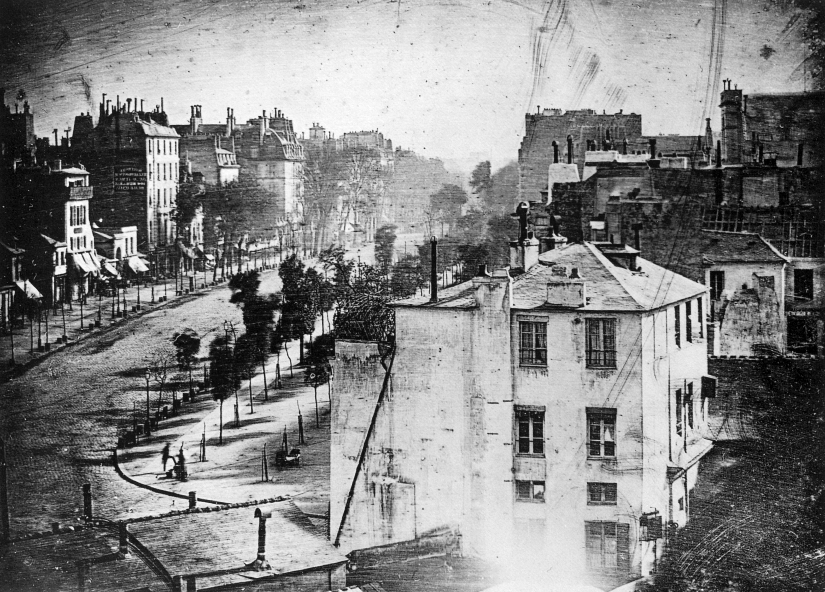 Made in 1838 by inventor Louis Daguerre, this is believed to be the earliest photograph showing a living person. It is a view of a busy street, but because the exposure lasted for several minutes the moving traffic left no trace. Only the two men near the bottom left corner, one apparently having his boots polished by the other, stayed in one place long enough to be visible.