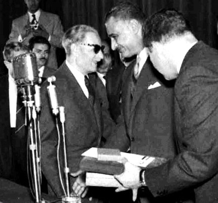 Two men conferring with each other, both are wearing suits and the man on the left is also wearing sunglasses. Three men are standing around them, with one holding a number of objects in his hand