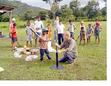 A Peace Corps volunteer playing tee-ball in Honduras.