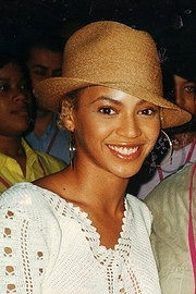 An image of a smiling woman wearing large hoop earrings and a beige hat. She is also wearing a white blouse and people can be seen standing behind her.