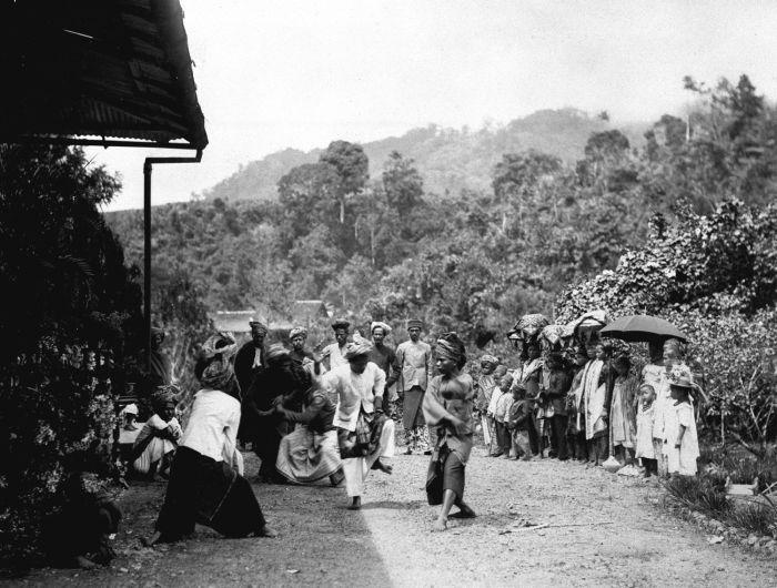 File:COLLECTIE TROPENMUSEUM Een groep feestelijk geklede Indonesische mannen vrouwen en kinderen bekijken een door gongs begeleide mannendans voor een Europese woning op Sumatra TMnr 60011332.jpg