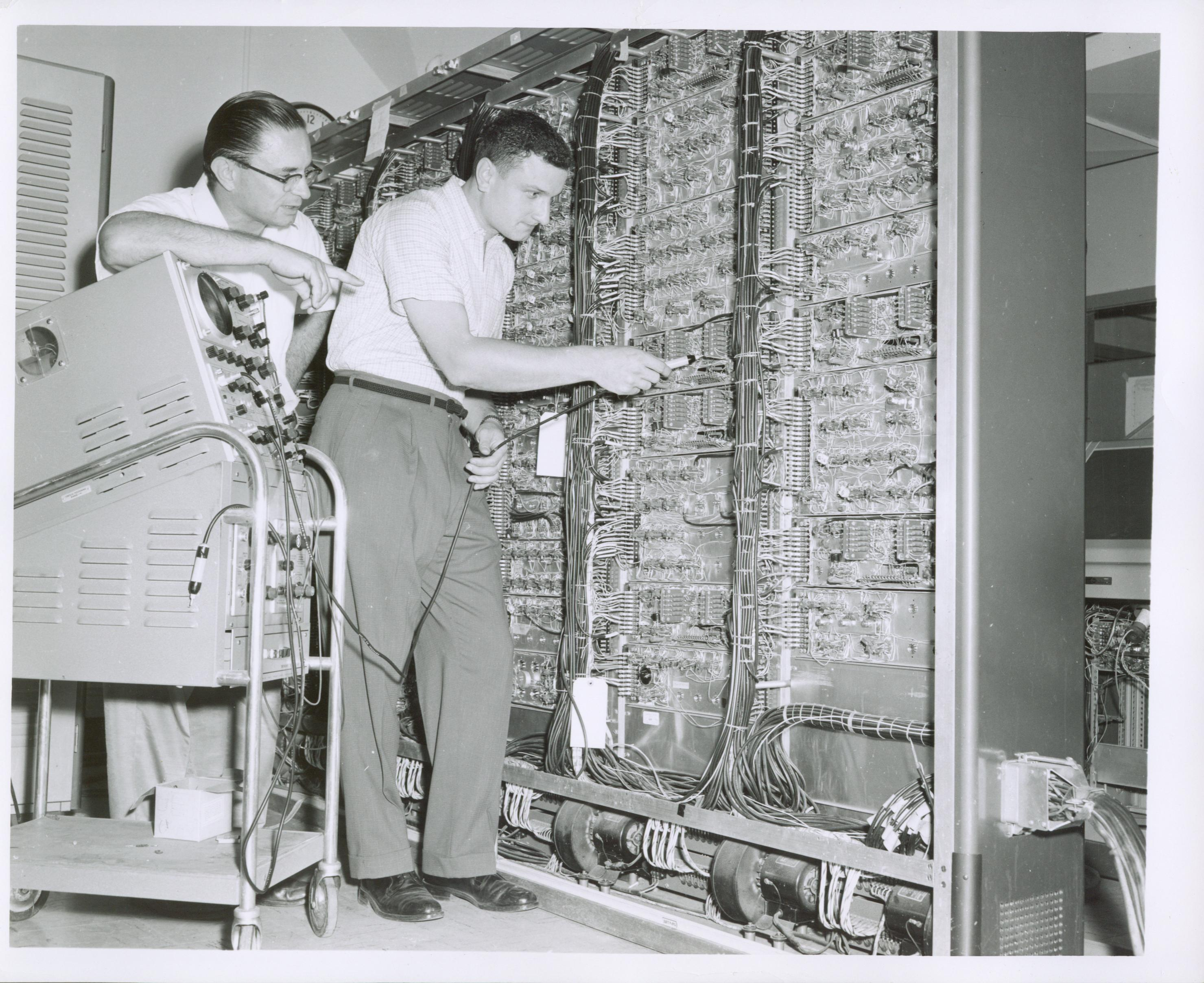two men testing electrical components of a Census bureau computer, 1950s