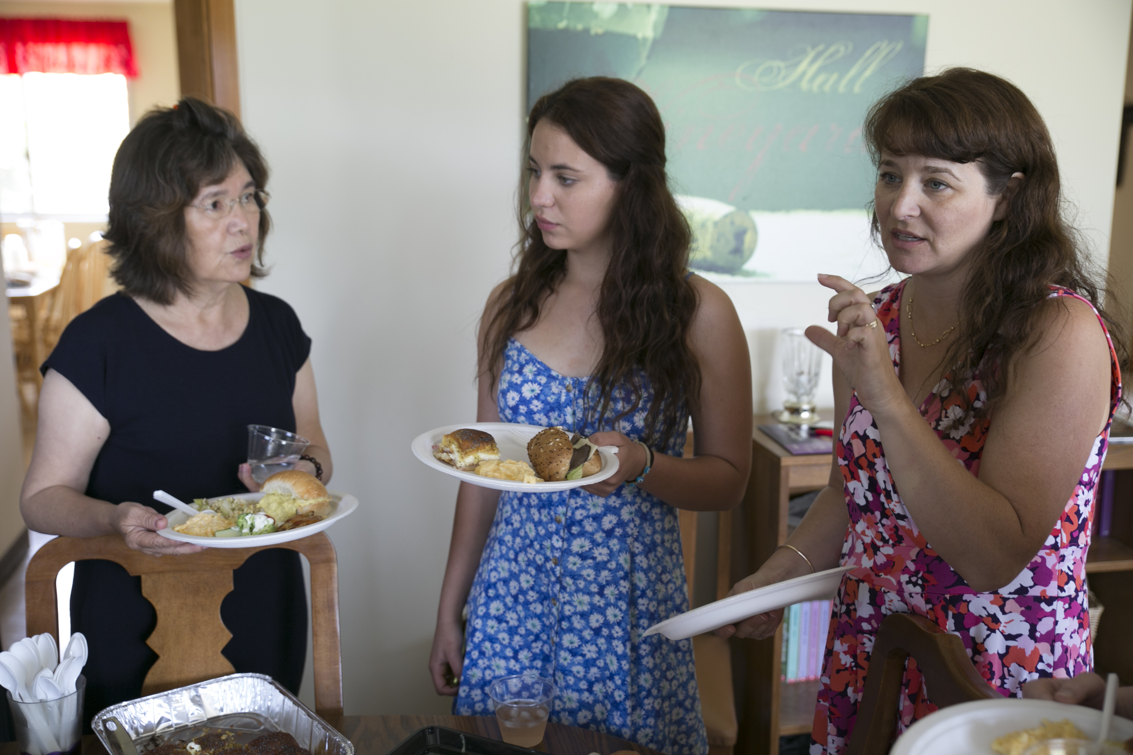 Three women standing with plates of food in their hands