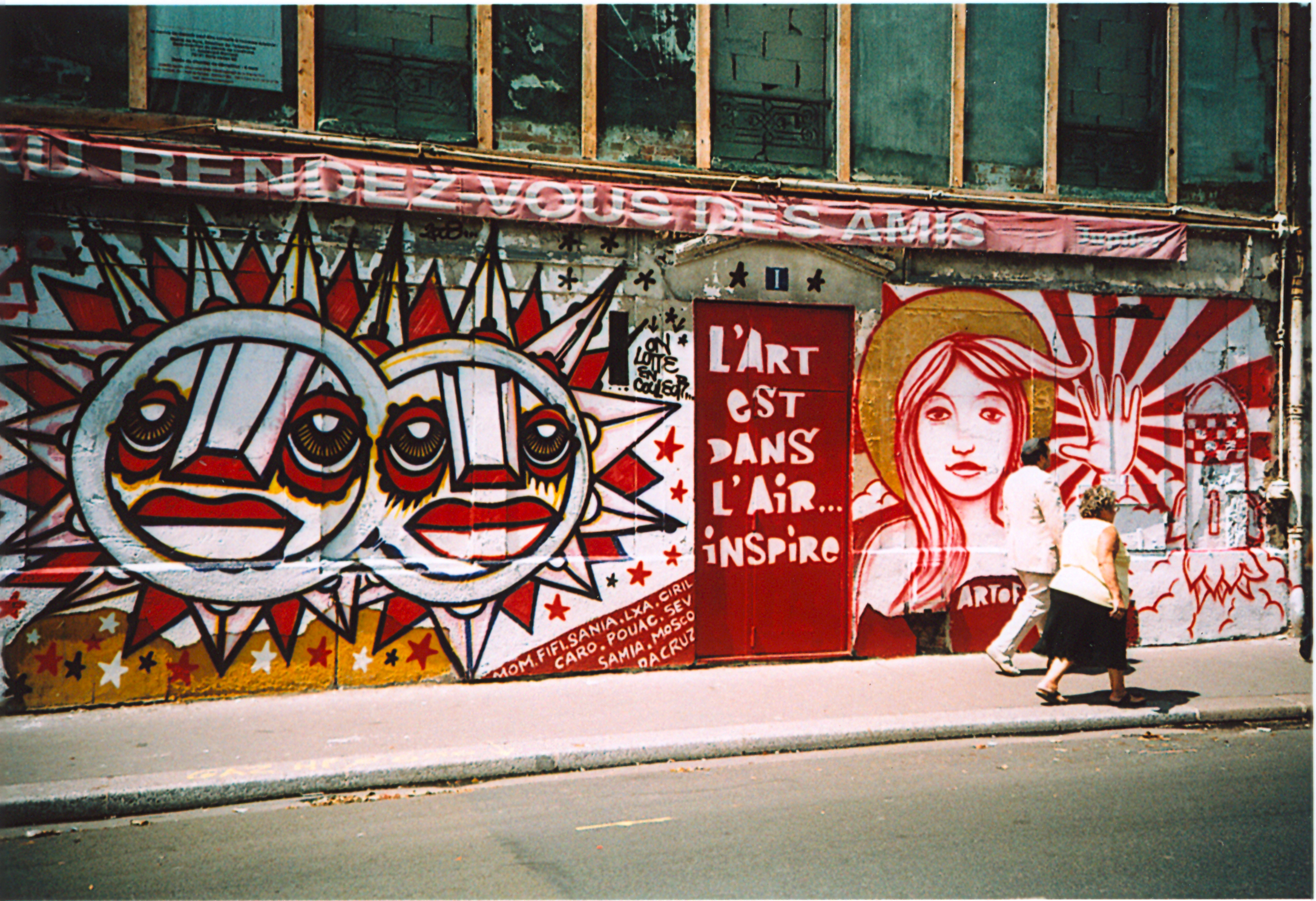 graffiti of suns and a woman holding up her hand, with the text: art is in the air ... inspires