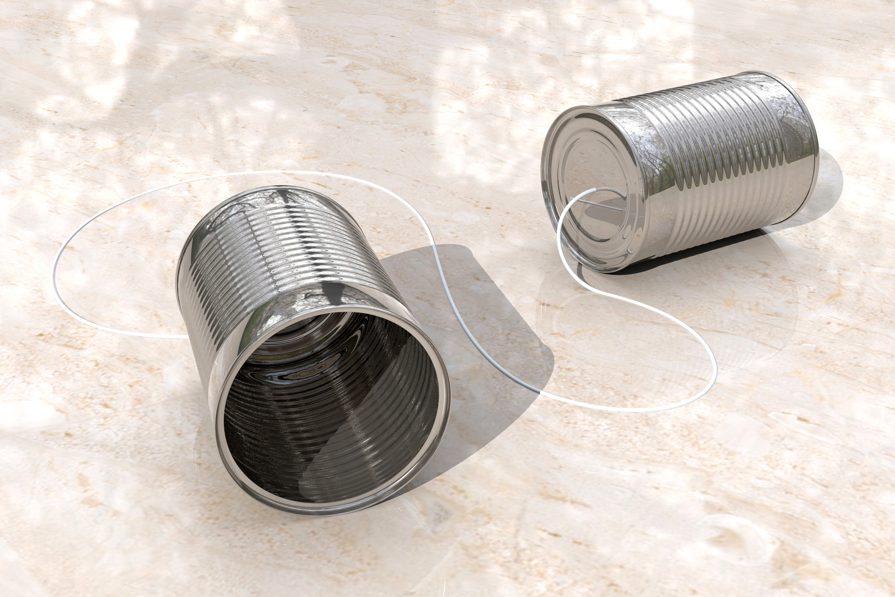 Two silver coloured tin cans are connected by a string. The open end of one can faces the viewer, while the open end of the other faces the right side of the picture. The cans are lying down on a cream marbled background.