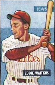 A baseball card image of a smiling man wearing a white baseball jersey striped with red and a red baseball cap holding a baseball bat over his shoulder