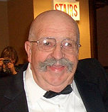 A photograph of a bald man with a grey moustache wearing glasses and a black tuxedo, looking at the camera, and holding a drinking glass