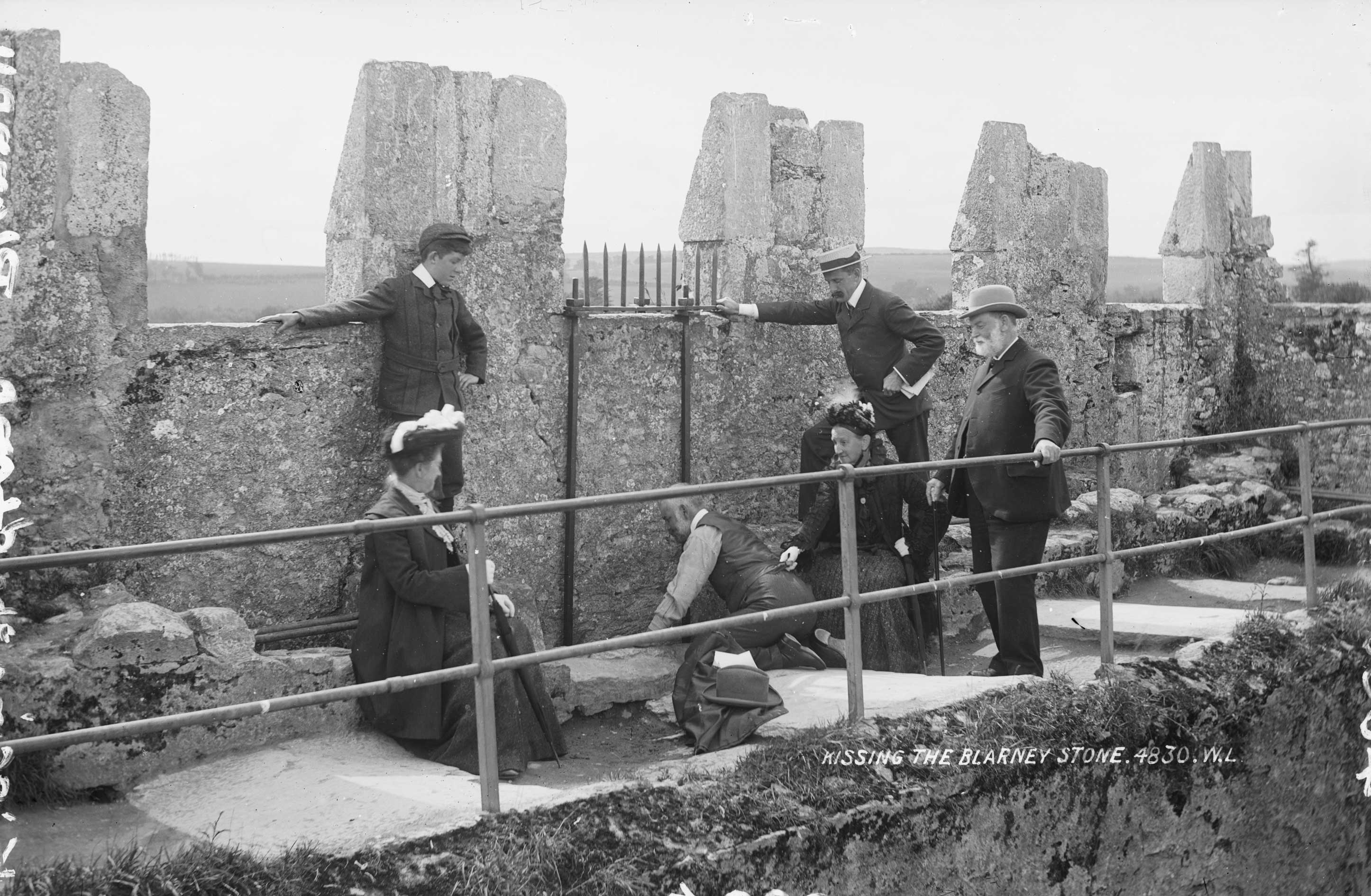 A black-and-white photo from 1897 showing a party of tourists at Blarney Castle with one of them kissing the Blarney Stone