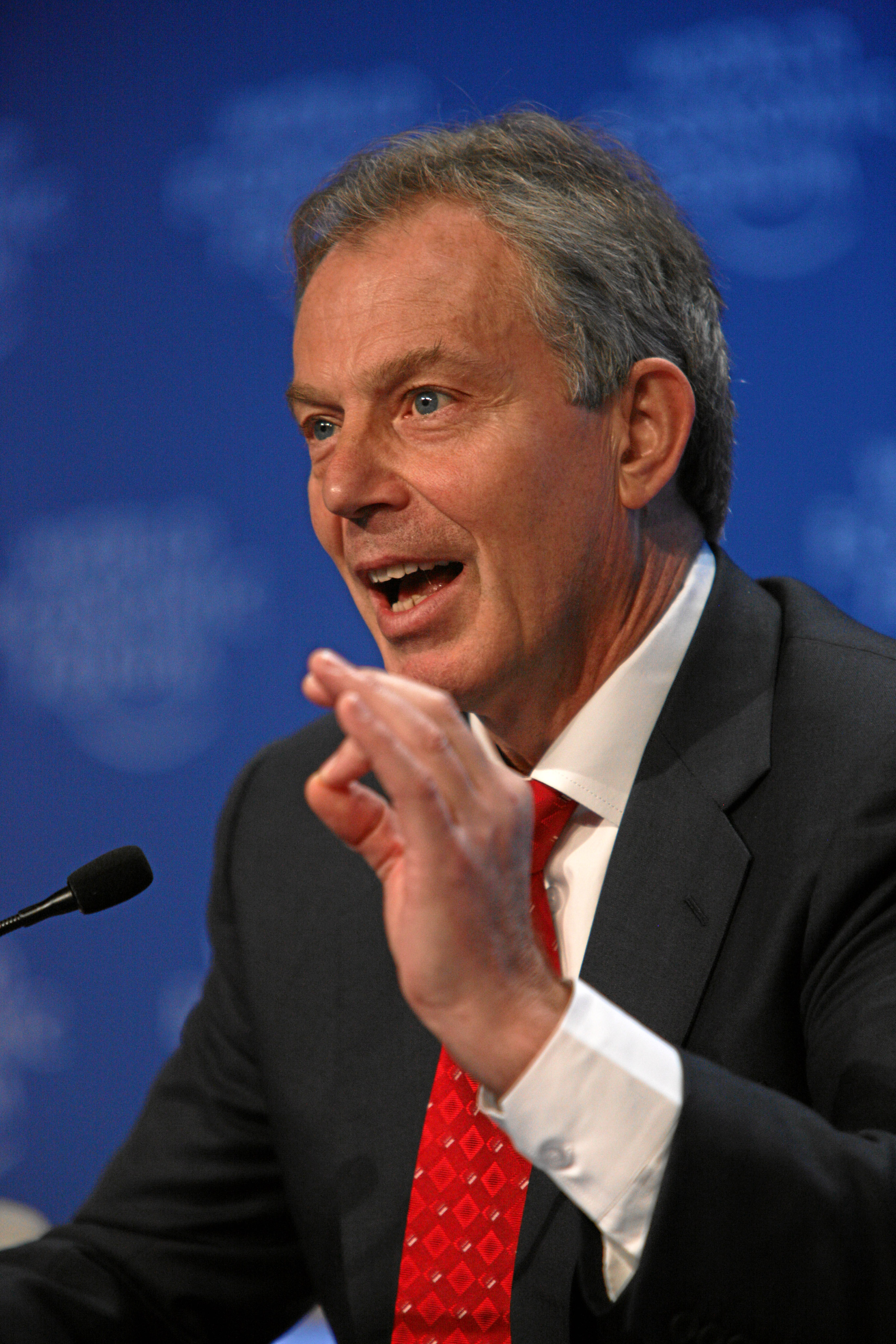 A photograph of a man with greying hair speaking into a microphone and gesturing with his left hand
