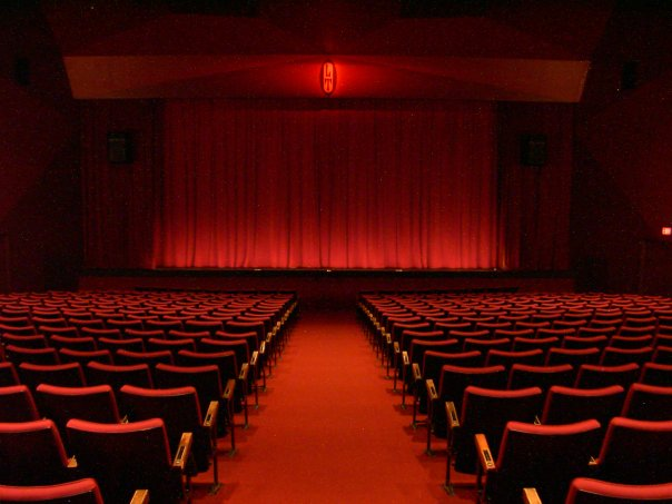 Photograph of red curtain and empty theatre.