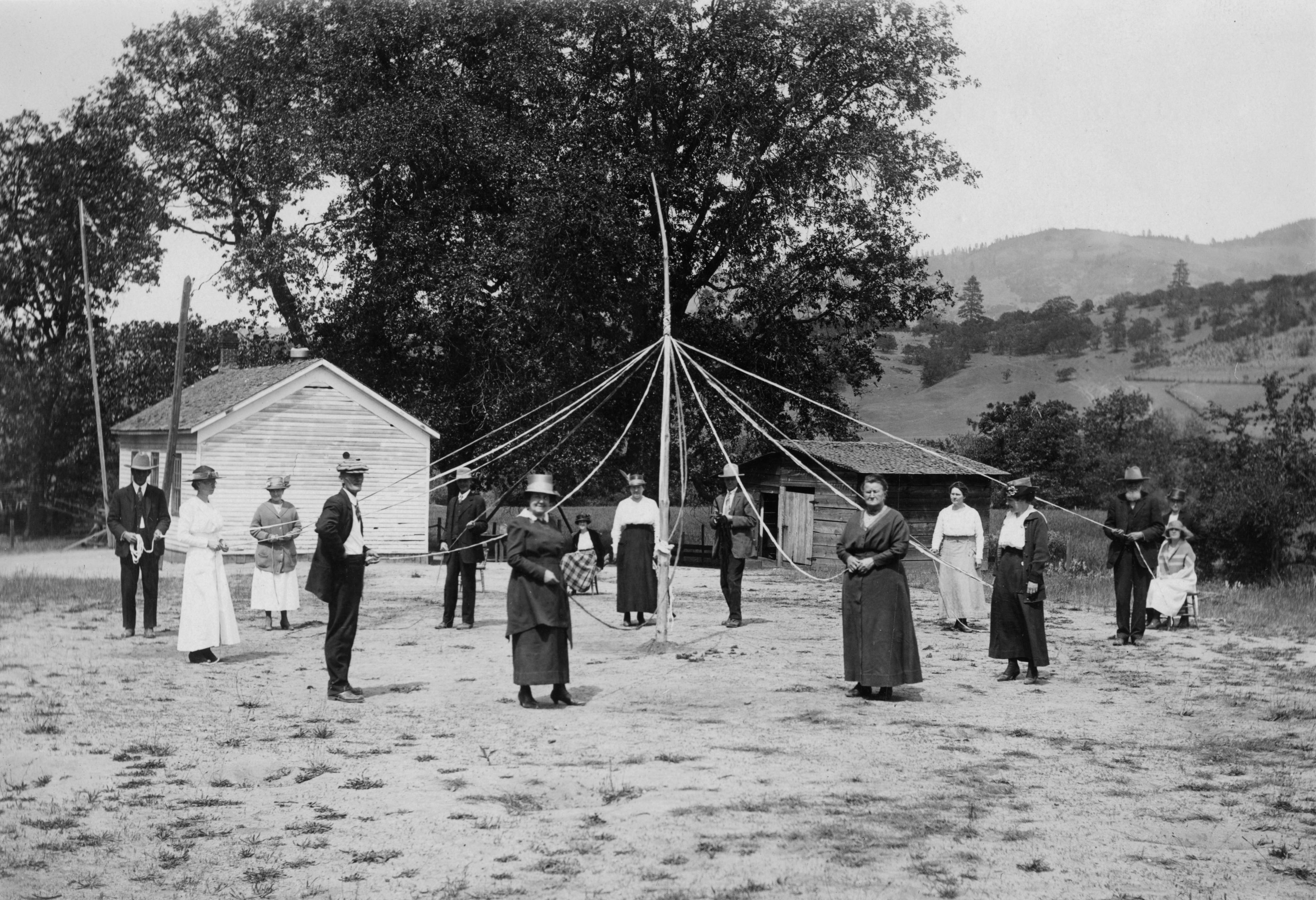 Black-and-white image of men and women holding the ribbons that connect to the top of a May Pole
