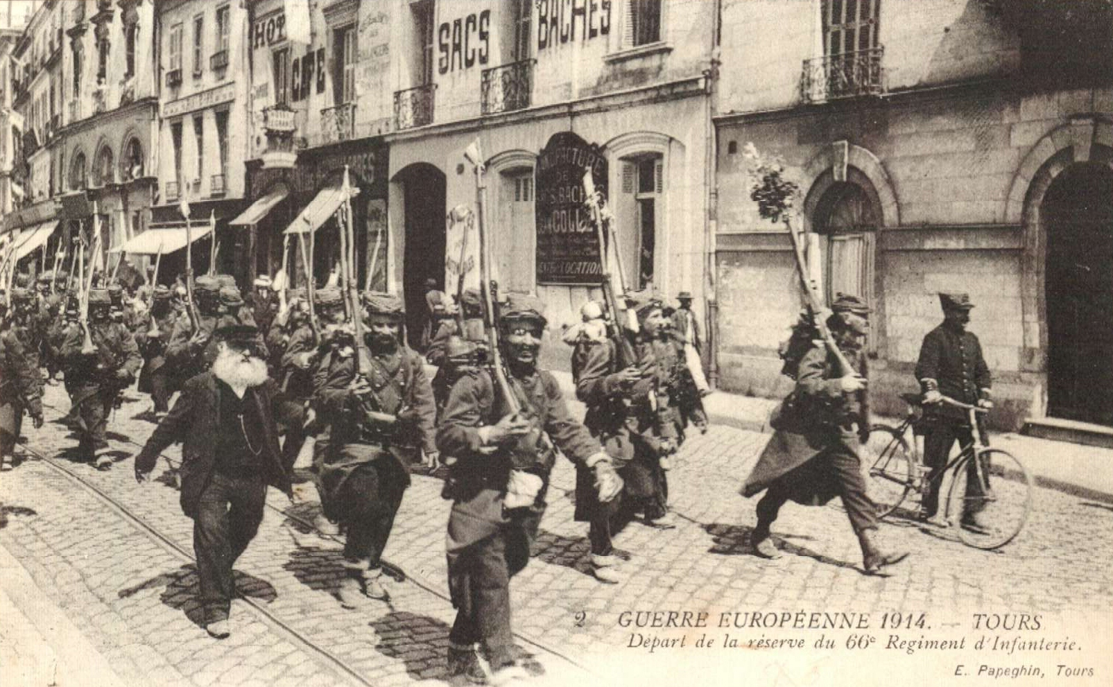Columns from the 66th Infantry Regiment marching with little flags or flowers in the barrel of their gun, towards Tours station on August 5th, 1914