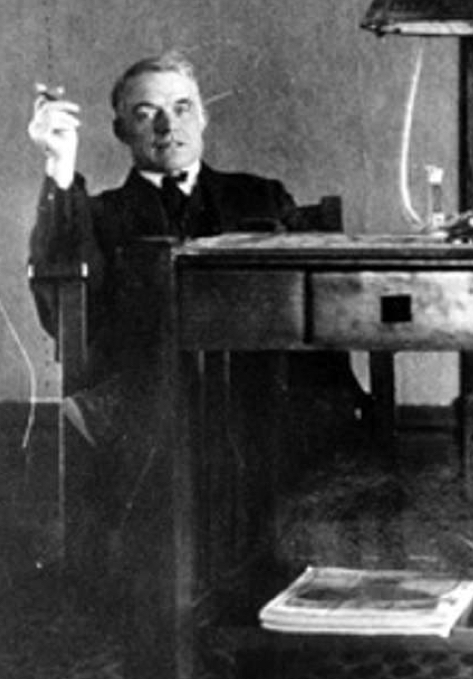 a single grey-haired man dressed in a dark suit and white shirt, is looking directly at the photographer, while sitting in a chair at a table while apparently holding up a cigar