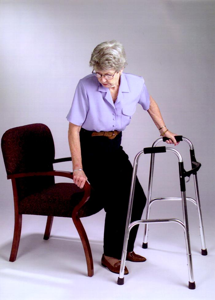 Woman with walker sitting down in a chair.