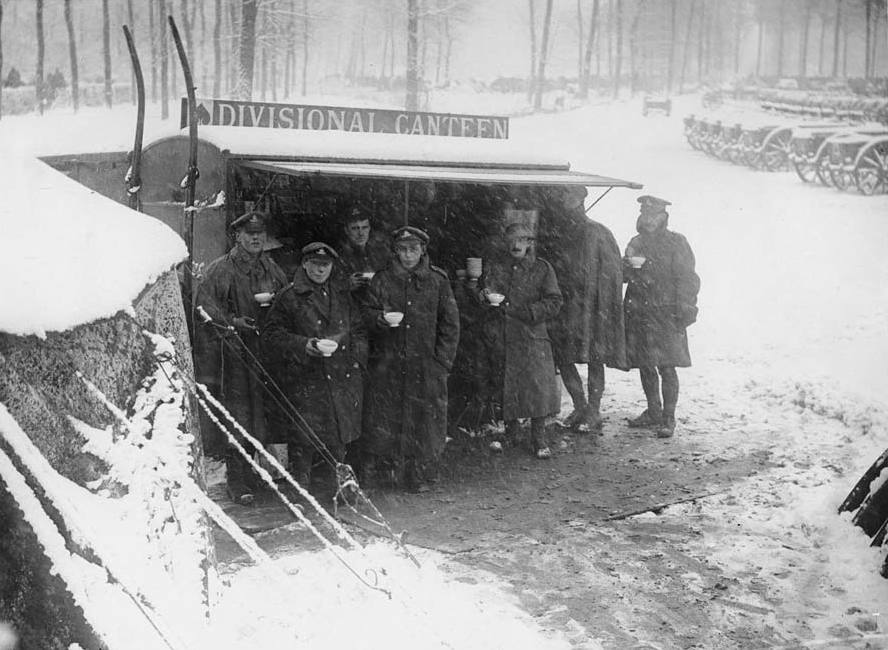 The photographer has recorded a group of soldiers sheltering from a blizzard at a mobile Divisional Canteen. Their cap badges identify the men as members of the Royal Regiment of Artillery. To the left alongside the road, there are a line of parked horse-drawn vehicles, which appear to be gun limbers, and men on horses are visible in the background.The men are drinking bowls of something hot. These men were lucky. Those in the trenches often had no really warm food for days on end. The food, cooked at a distance behind the lines, was often cold before it reached the soldiers. [Original reads: 'Snow at the front. The cup that cheers.'] http://digital.nls.uk/74549288