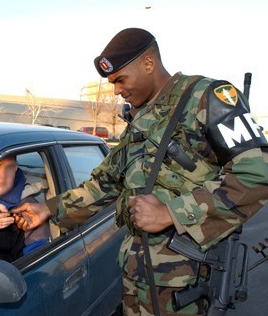 Spc. Patrick Jean-Mary, of Warwick, R.I., inspects two forms of identification during the 2002 Winter Olympic Games in Salt Lake City WinterOlympicsMP2002.png